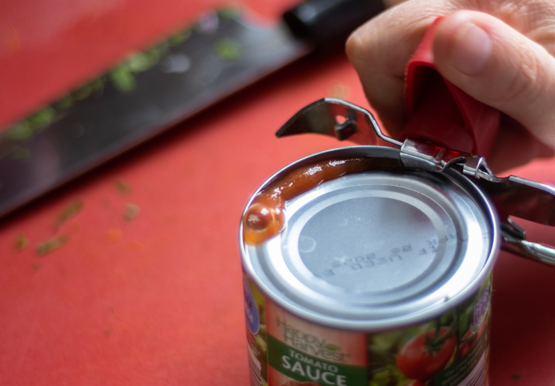 Hands using a can opener to open a can of tomato sauce.