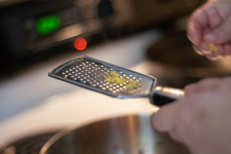 Hands using a grater to grate ginger into a pan.