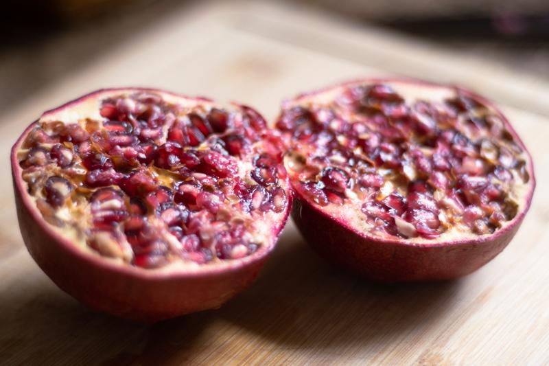 Closeup of a pomegranate cut in half on a wooden cutting board.