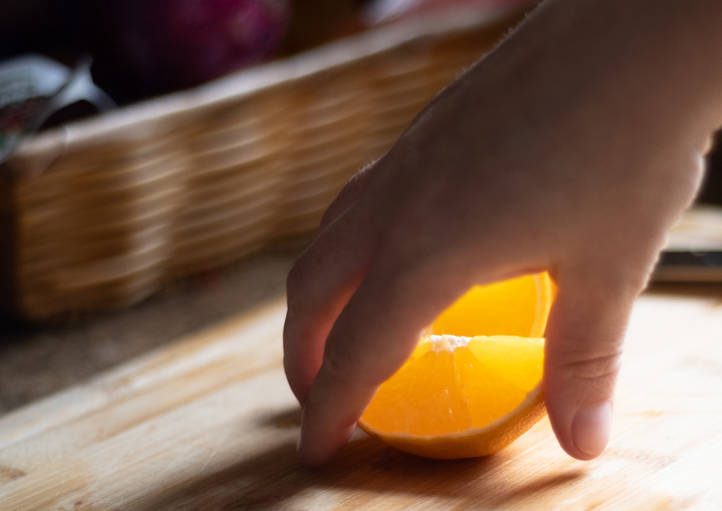Closeup of hands reaching for orange wedges.