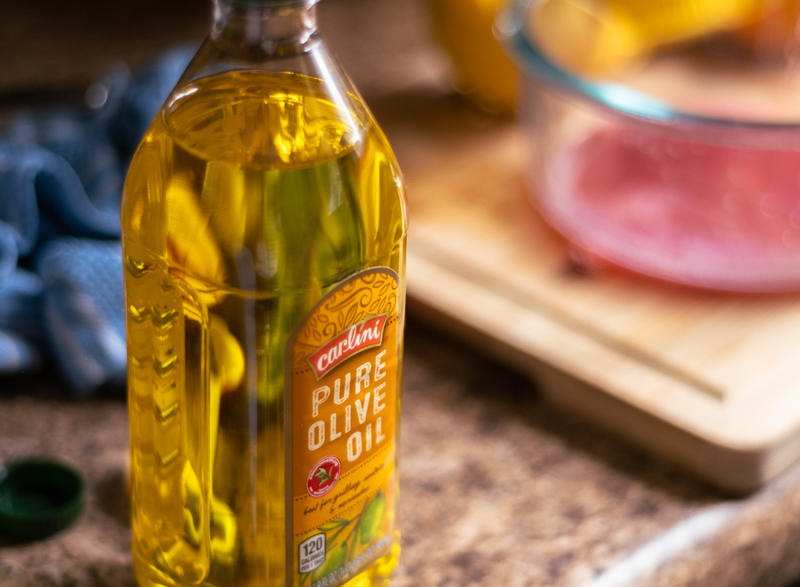 Closeup of bottle of olive oil with bowl of salad dressing ingredients in the background.