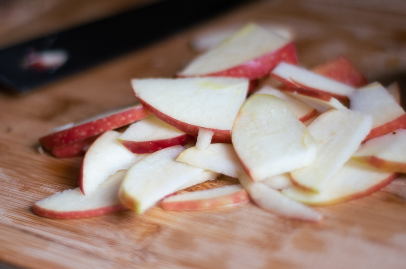 Closeup of apple slices cut into bite-sized pieces on a wooden cutting board.