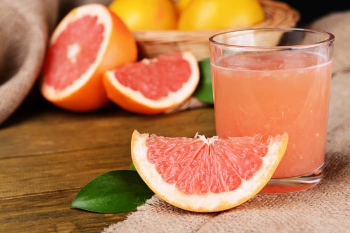 Closeup of glass of pink-colored grapefruit juice with a wedge of pinkish red grapefruit next to it and in background.