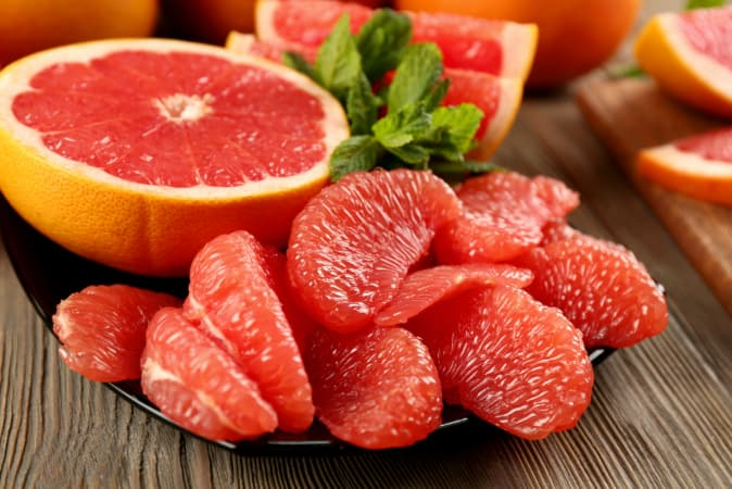 Closeup of a plate of grapefruit slices garnished with mint.  These grapefruit recipes will show you that fresh isn't the only way to enjoy grapefruit.