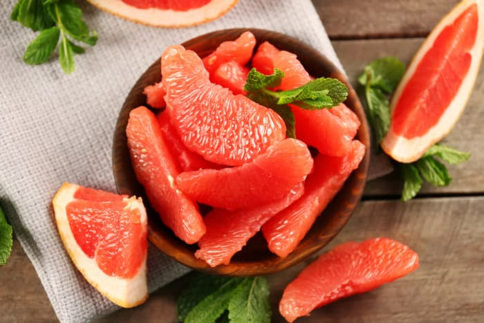 Overhead view of bowl of reddish pink grapefruit slices.