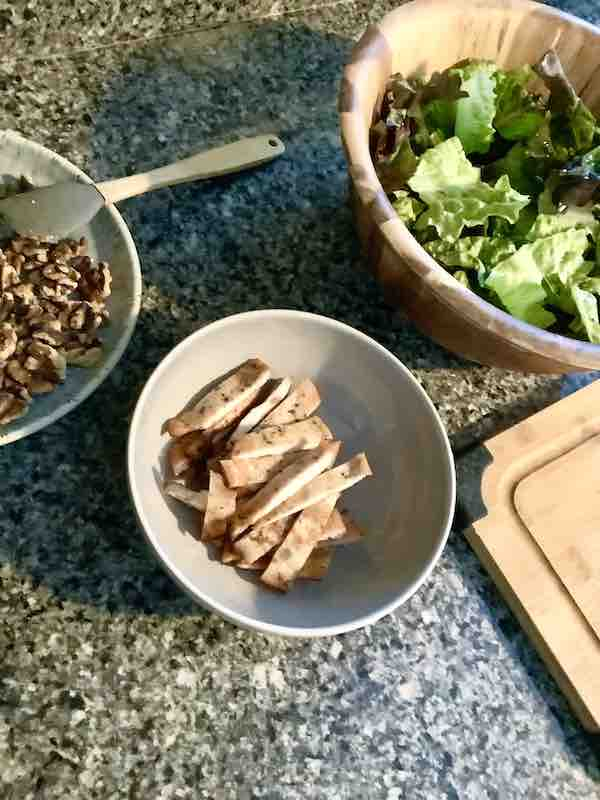 Bowl of sliced chicken breast next to a bowl of salad green and a bowl of toasted walnuts.
