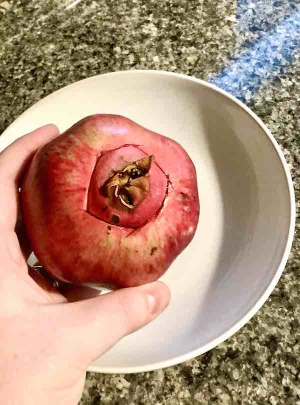 To remove the arils from the pomegranate cut a circle around the stem.