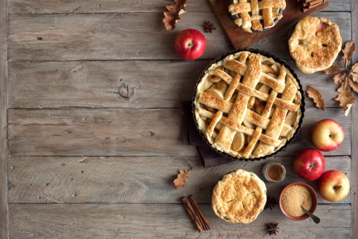 Overhead view of a large apple pie, smaller apple pies, and whole apples on a wooden table.