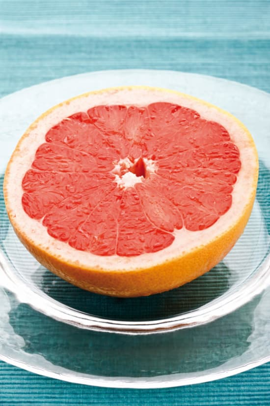 Closeup of a half of a Star Ruby grapefruit on a plate.