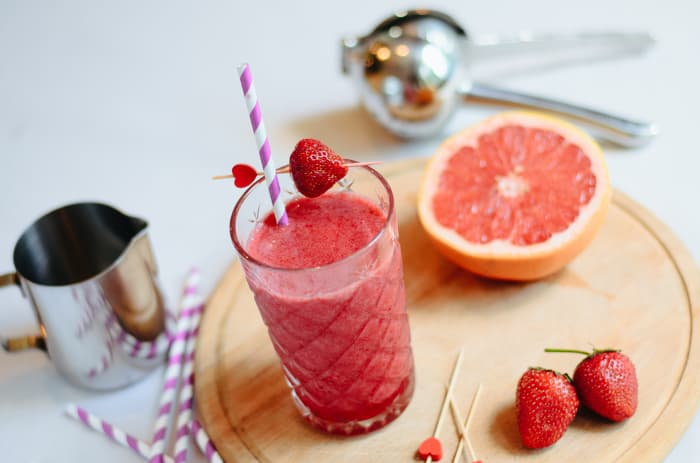 Overhead view of a strawberry grapefruit smoothie in a class with a straw.